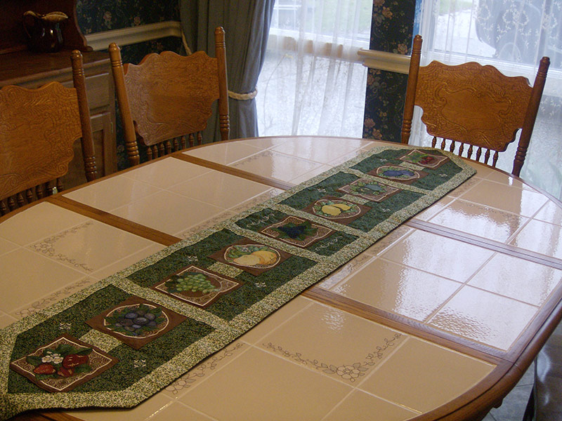 Hand-crafted table runner and matching place mats with various fruit embroidery designs.